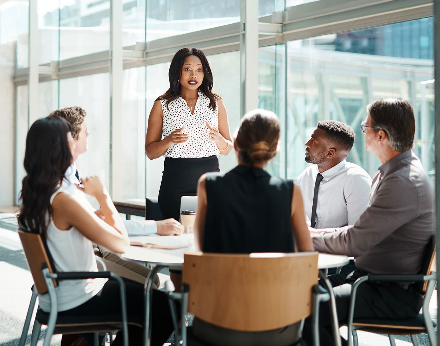 Image of women standing and presenting to a group of five professionals sitting at a deck dressed professionally
