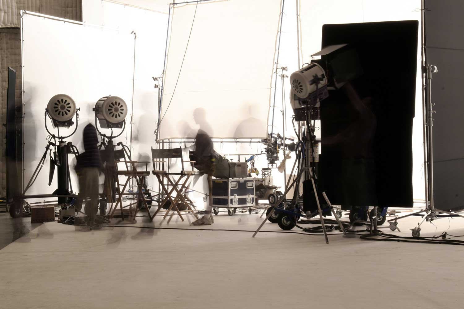 Image of people working on set. Lights can be seen.